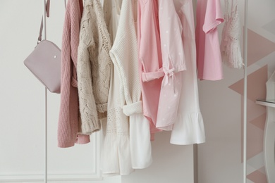 Rack with stylish clothes near white wall in dressing room