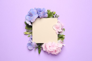 Beautiful hortensia flowers and blank card on violet background, flat lay. Space for text