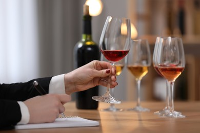 Sommelier tasting different sorts of wine at table indoors, closeup