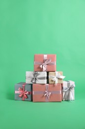 Many beautifully wrapped gift boxes on green background