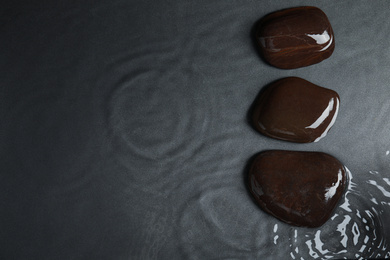 Stones in water on grey background, flat lay with space for text. Zen lifestyle