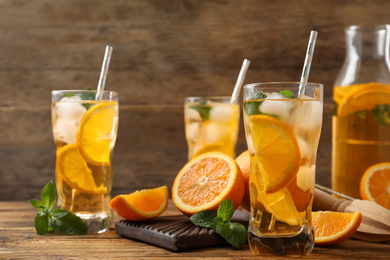 Delicious refreshing drink with orange slices on wooden table