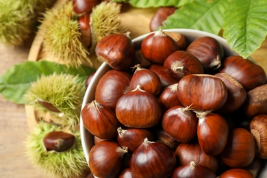 Fresh sweet edible chestnuts in bowl on table, top view