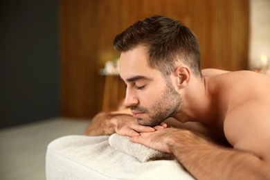 Handsome man relaxing on massage table in spa salon