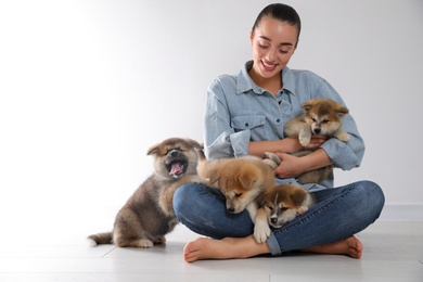 Woman with Akita Inu puppies sitting on floor near light wall. Space for text