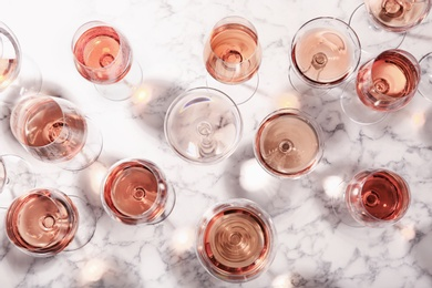 Different glasses with rose wine on marble background, flat lay
