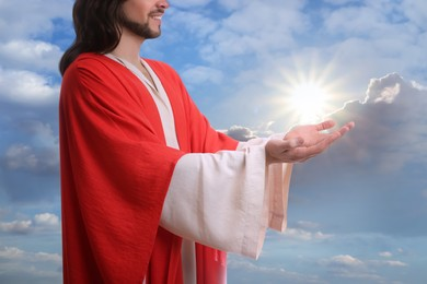 Jesus Christ reaching out his hands and praying against blue sky