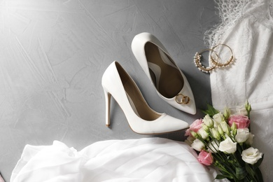 Flat lay composition with wedding dress, white high heel shoes and flowers on grey background. Space for text