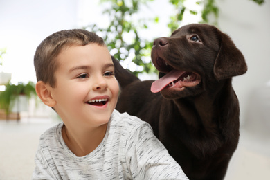 Little boy playing with puppy at home. Friendly dog