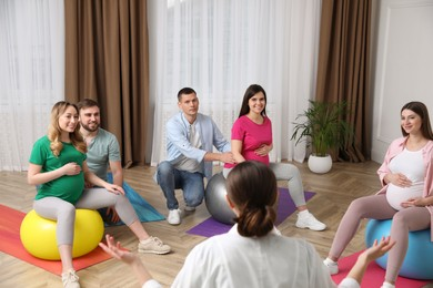 Pregnant women with men and doctor at courses for expectant parents indoors