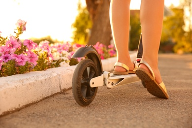 Woman riding electric kick scooter outdoors on sunny day, closeup