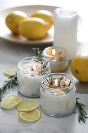 Natural homemade mosquito repellent candles and ingredients on white table