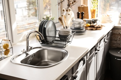 Stylish kitchen with sink and clean dishware