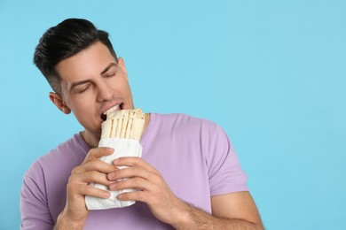 Man eating delicious shawarma on turquoise background, space for text