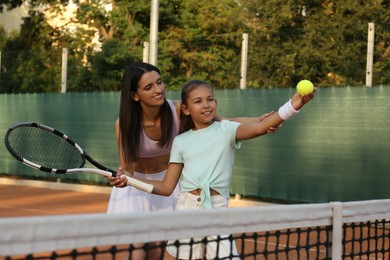 Mother teaching daughter to play tennis on court