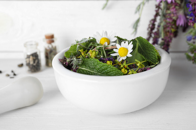 Mortar with healing herbs and pestle on white wooden table, closeup
