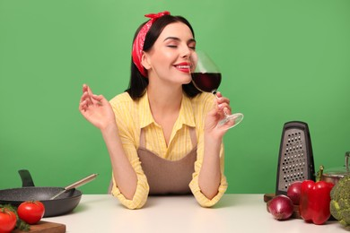 Young housewife with glass of wine, vegetables and different utensils on green background