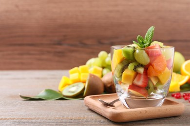 Delicious fresh fruit salad in dish on wooden table, space for text