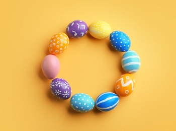 Frame made of painted Easter eggs on color background, top view. Space for text