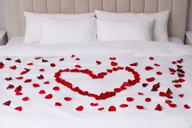 Beautiful heart of red rose petals on bed