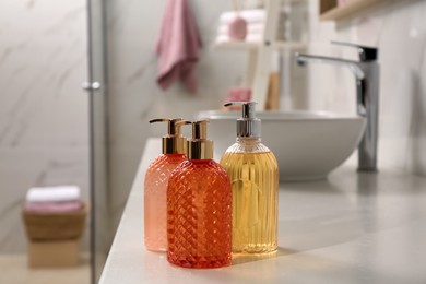 Glass dispensers with liquid soap on white table in bathroom