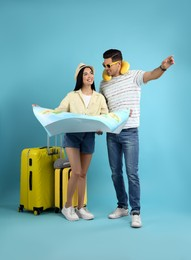 Couple of tourists with map and suitcases on light blue background