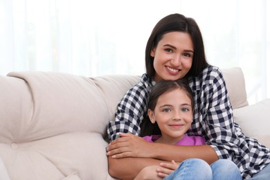 Portrait of happy mother and daughter on sofa at home. Single parenting