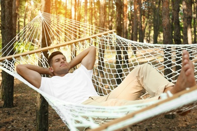 Handsome man resting in hammock outdoors on summer day