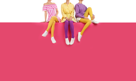 Group of women wearing bright tights and stylish shoes sitting on color background, closeup