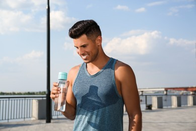 Handsome man in sportswear with bottle of water outdoors on sunny day
