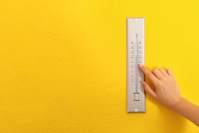 Woman with weather thermometer on yellow background, closeup. Space for text