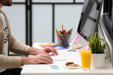 Male designer working at desk in office, closeup