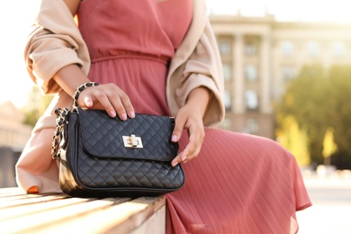 Young woman with stylish black bag on bench outdoors, closeup