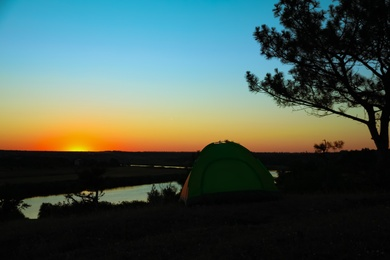 View of tent near river in evening