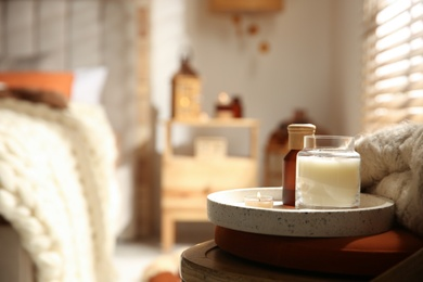 Burning candles on wooden chair in bedroom, space for text. Interior elements