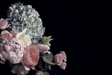 Beautiful bouquet of different flowers on black background, space for text. Floral card design with dark vintage effect