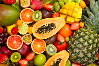 Many different delicious exotic fruits as background, top view