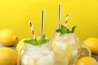 Natural freshly made lemonade with mint on yellow background, closeup. Summer refreshing drink