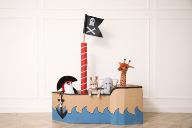 Pirate cardboard ship and toys near white wall indoors