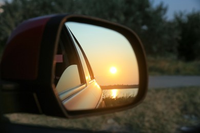 Reflection of landscape with beautiful sunset over calm river in car side view mirror, closeup