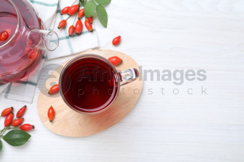 Flat lay composition with aromatic rose hip tea on white wooden table. Space for text