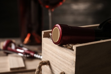 Open wooden crate with bottle of wine on blurred background