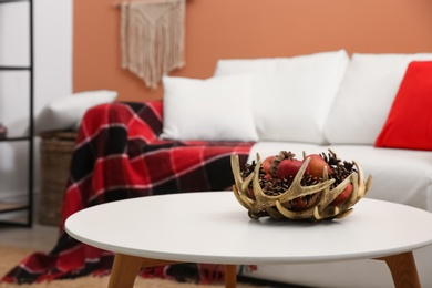Decorative antler bowl with apples and pine cones in living room interior inspired by autumn colors
