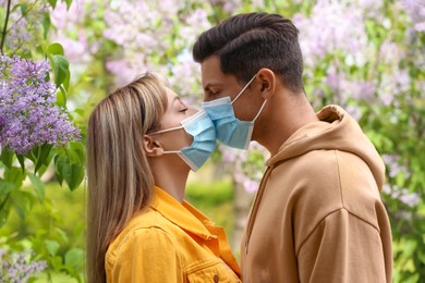 Couple in medical masks trying to kiss outdoors