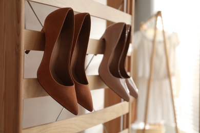 Rack with stylish women's high heeled shoes in dressing room. Modern interior design