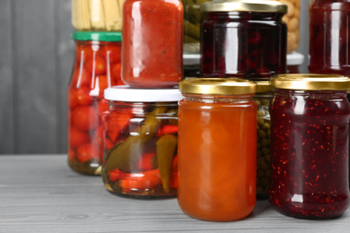 Glass jars with different pickled foods on grey wooden background, closeup