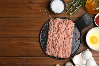 Raw chicken minced meat and ingredients on wooden table, flat lay. Space for text