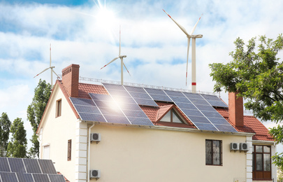 Wind turbines near house with installed solar panels on roof. Alternative energy source