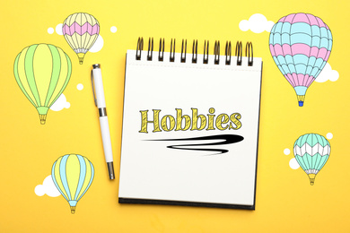Notebook with word Hobbies and pen on yellow background, top view