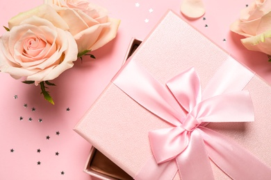 Elegant gift box, beautiful flowers and confetti on pink background, flat lay